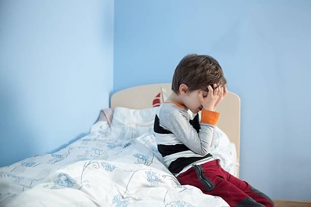 traurige kleine junge sitzt auf dem rand von seinem bett. - bett für jungs stock-fotos und bilder