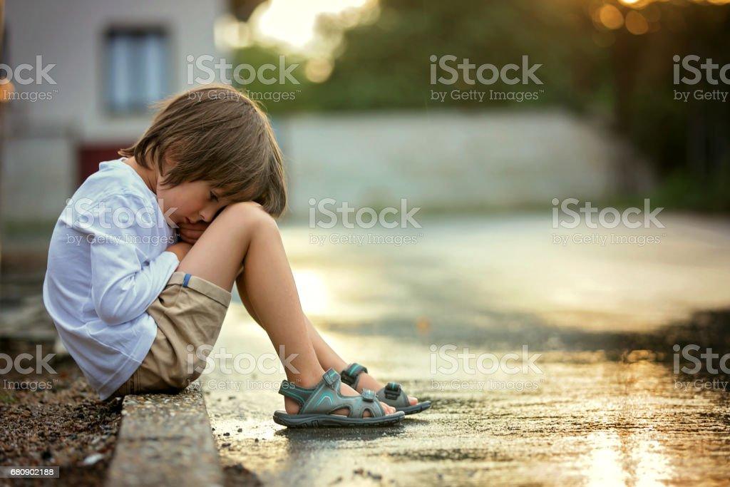 Sad little boy, sitting on the street in the rain, hugging his teddy bear, summertime on sunset royalty-free stock photo