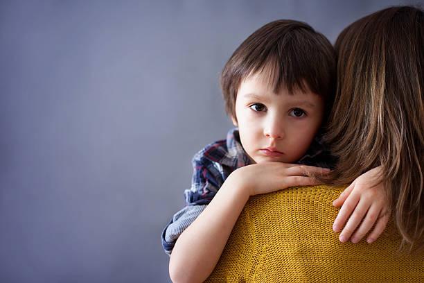 traurige kleine kind-jungen und seine mutter umarmen zu hause fühlen - trauer verlust stock-fotos und bilder
