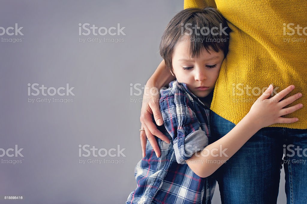 Sad little child, boy, hugging his mother at home stock photo