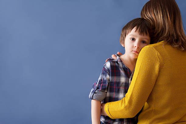 Cтоковое фото Печальный маленький ребенок, мальчик, подчеркивая его мать дома