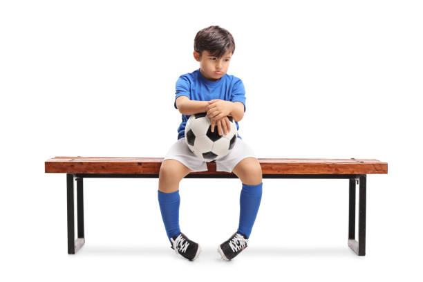 sad little footballer sitting on a wooden bench - criança perdida imagens e fotografias de stock
