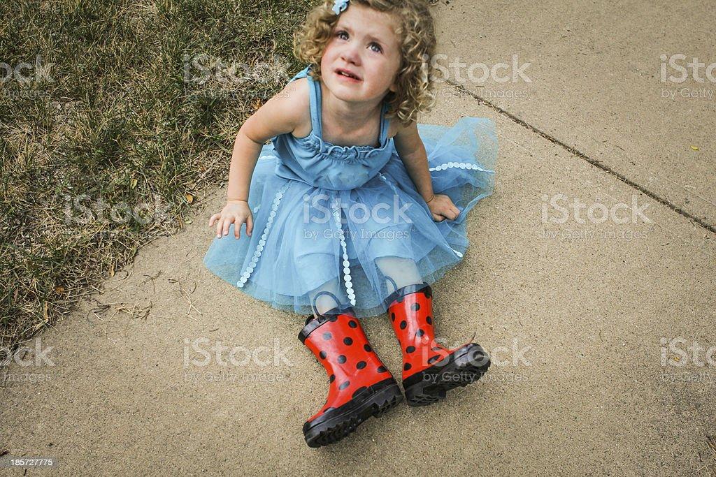 Sad little girl and rain boots stock photo
