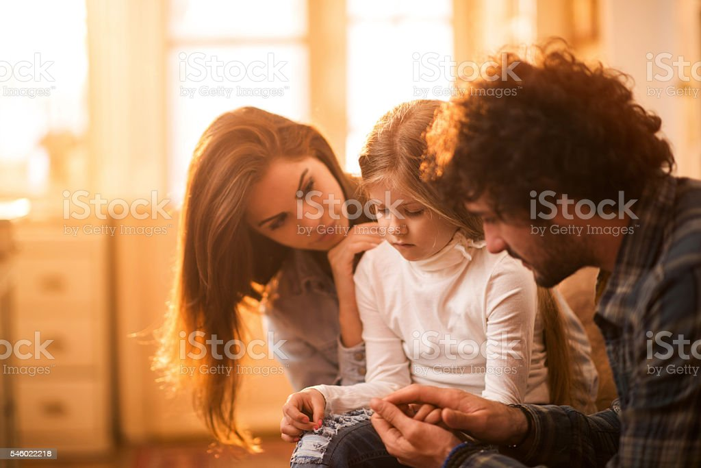 Sad little girl at home being consoled by her parents. stock photo