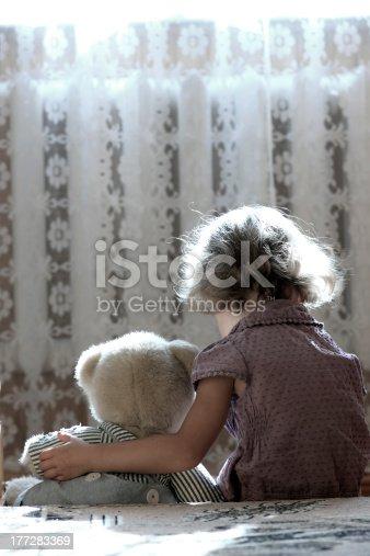 istock A sad little girl cuddles her teddy bear 177283369