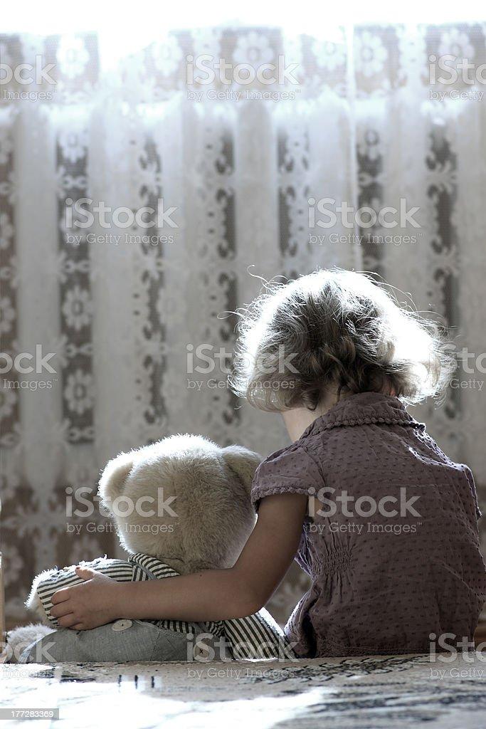 A sad little girl cuddles her teddy bear stock photo