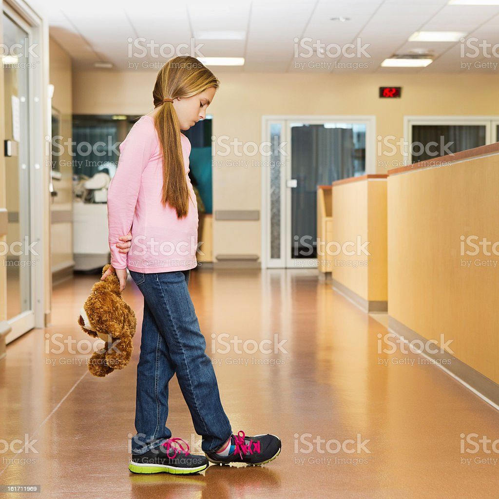 Sad little girl holding teddy bear in hospital hallway royalty-free stock photo