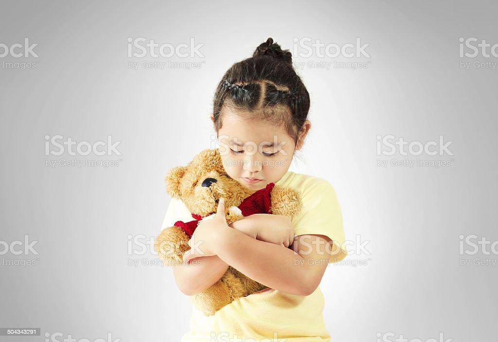 Sad little girl hugging teddy bear alone stock photo