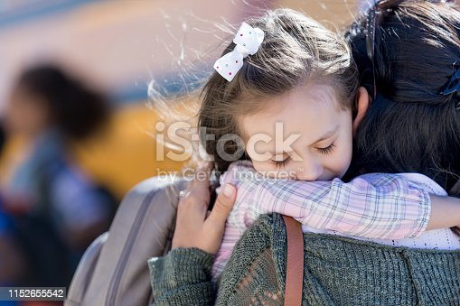 Worried little girl hugs her mom on the first day of school. A school bus is in the background.