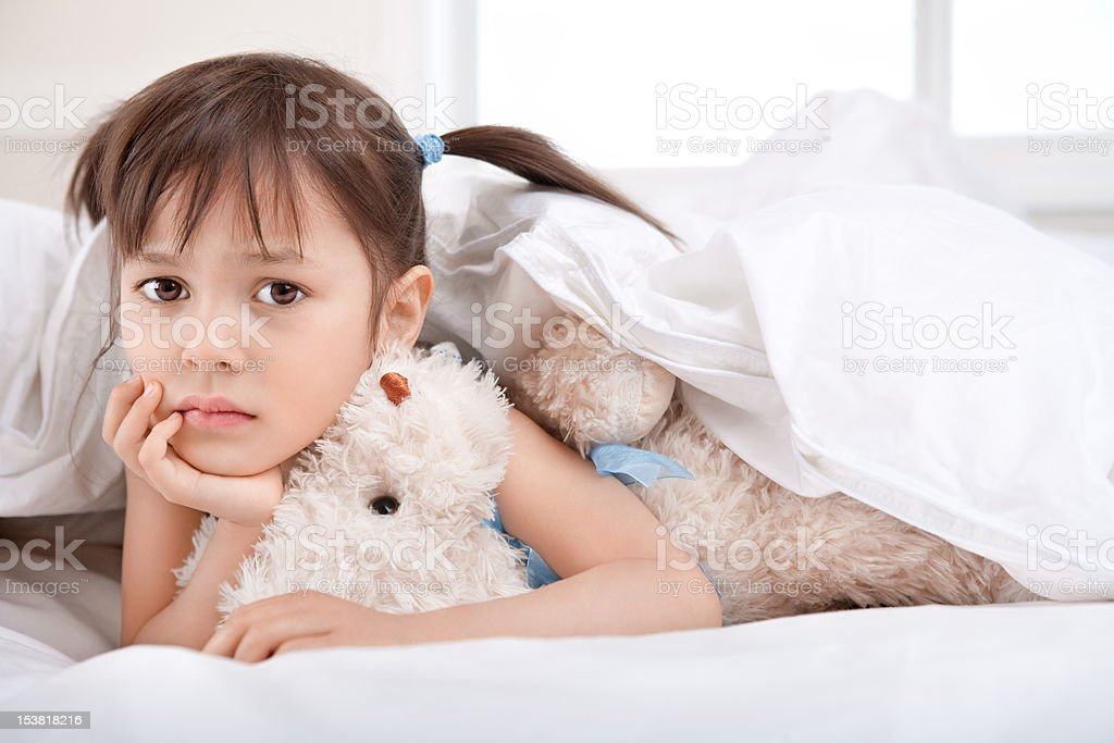 Sad little girl laying under blanket with teddy bear royalty-free stock photo