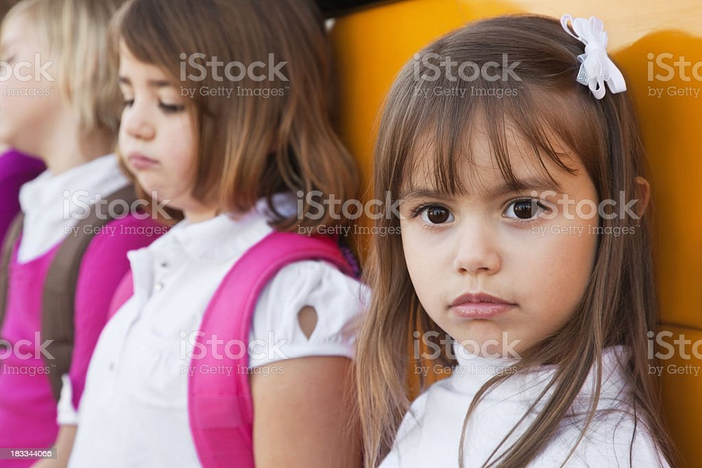 Sad Little Girl Looking Away With Students at School Bus.See more...