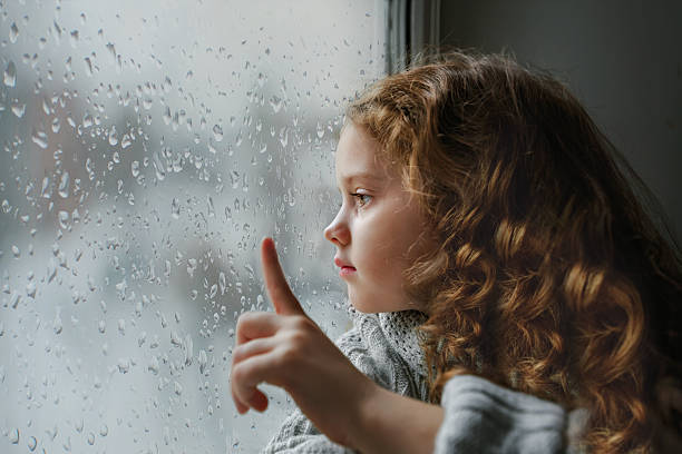 Sad little girl looking out the window. – Foto