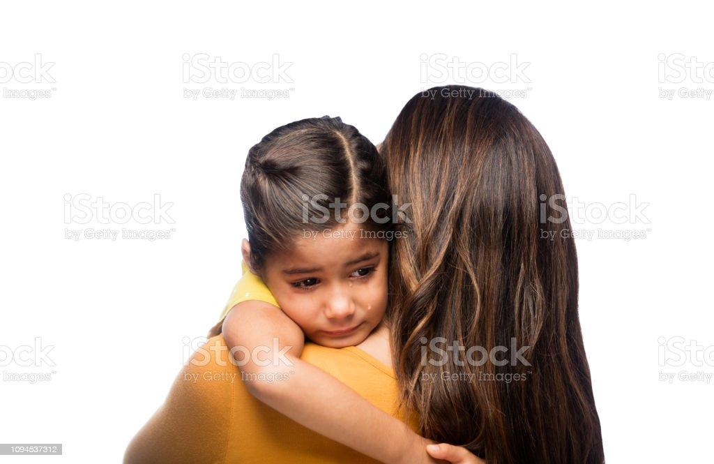 Sad little girl resting on her mother's shoulder stock photo
