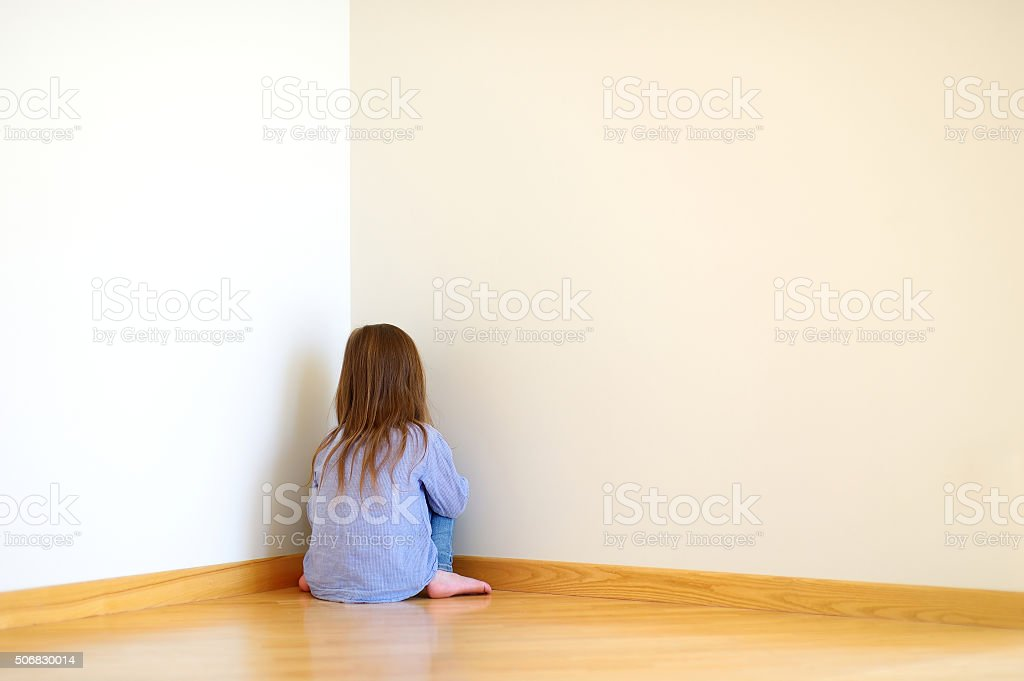 Sad little girl sitting in a corner stock photo
