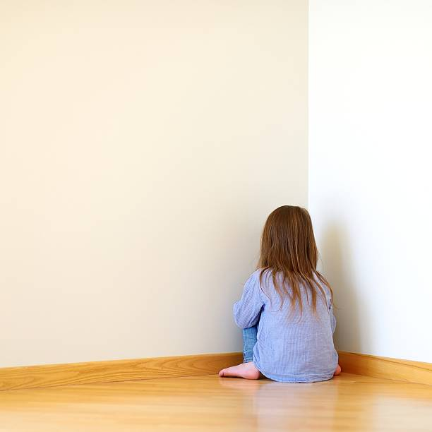 Sad little girl sitting in a corner Very sad little girl sitting on a floor at home shock tactics stock pictures, royalty-free photos & images