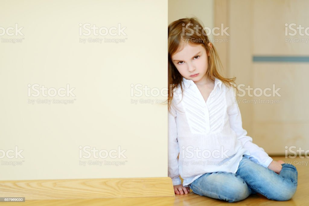 Sad little girl sitting on a floor stock photo