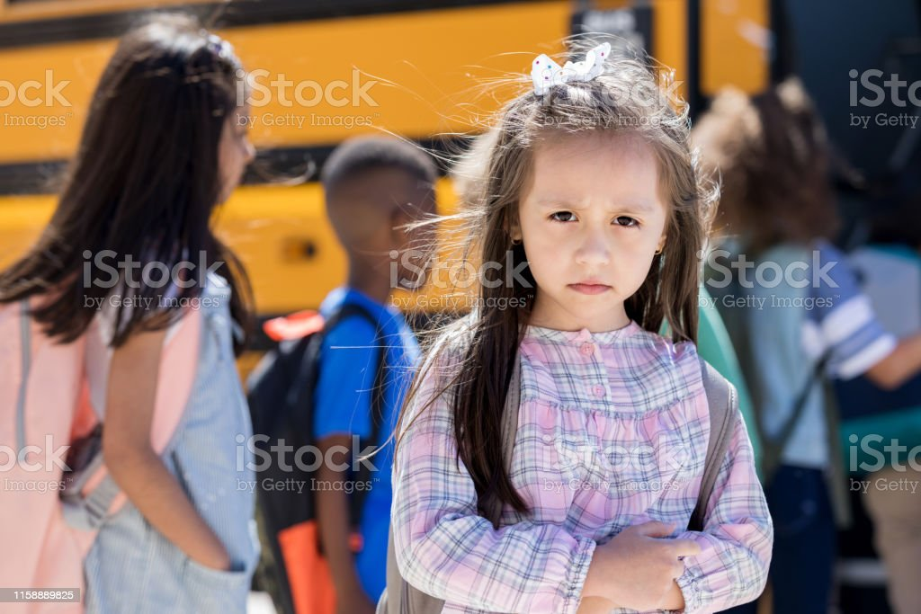 Elementary school girl looks sadly at the camera while standing in...