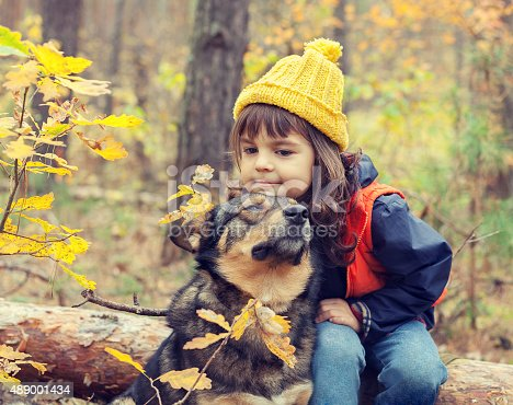 istock Sad little girl walking with dog in the fores 489001434