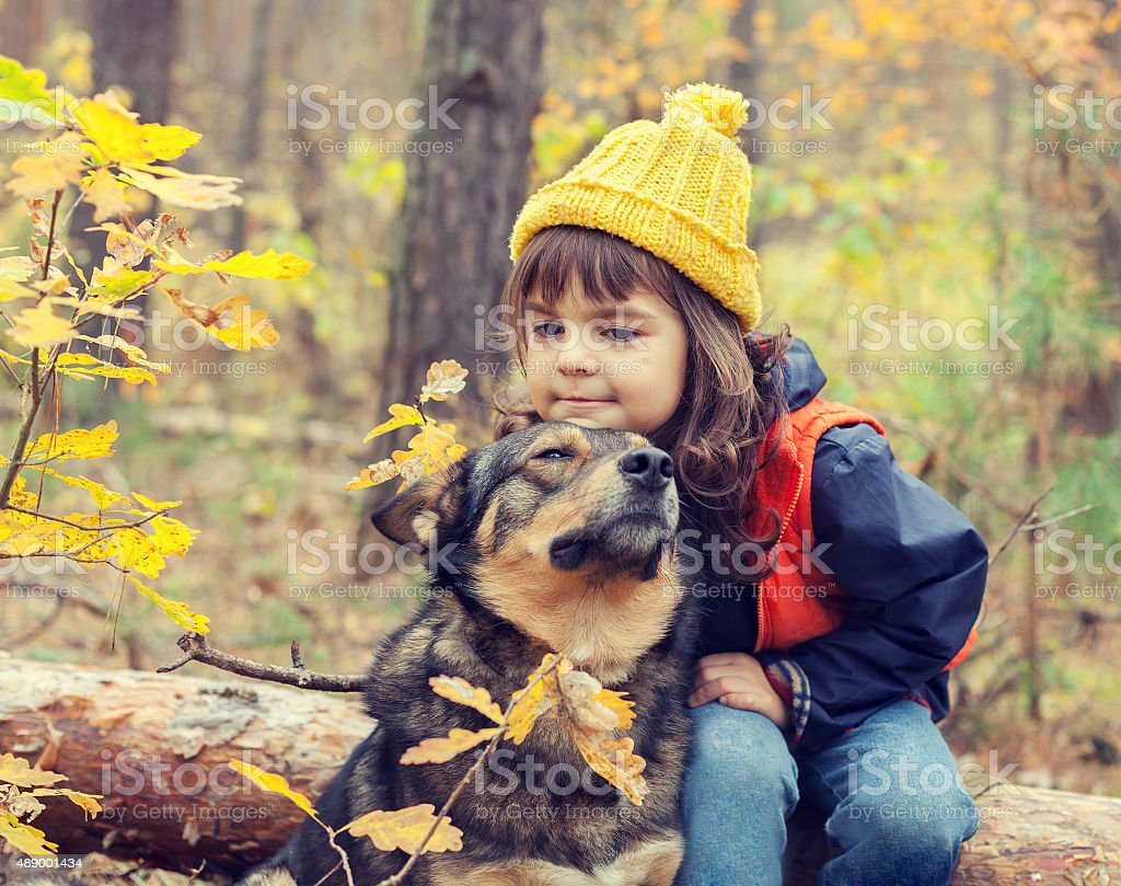 Sad little girl walking with dog in the fores stock photo