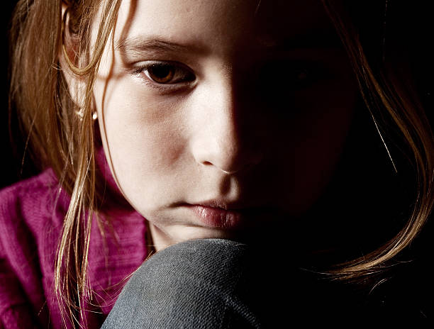 Sad little girl with chin resting on knee stock photo