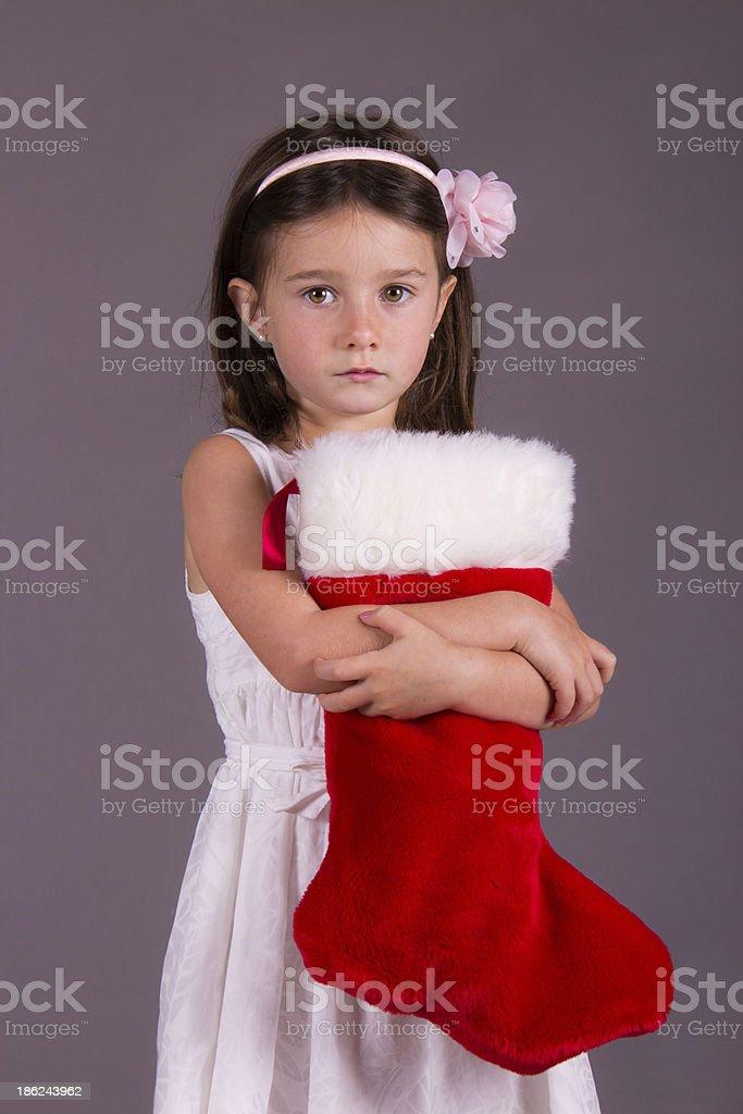 Sad little girl with Christmas stocking stock photo