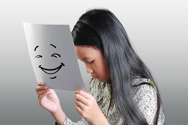 trauriges kleines mädchen mit glückliches gesicht maske - camouflagekleidung mädchen stock-fotos und bilder