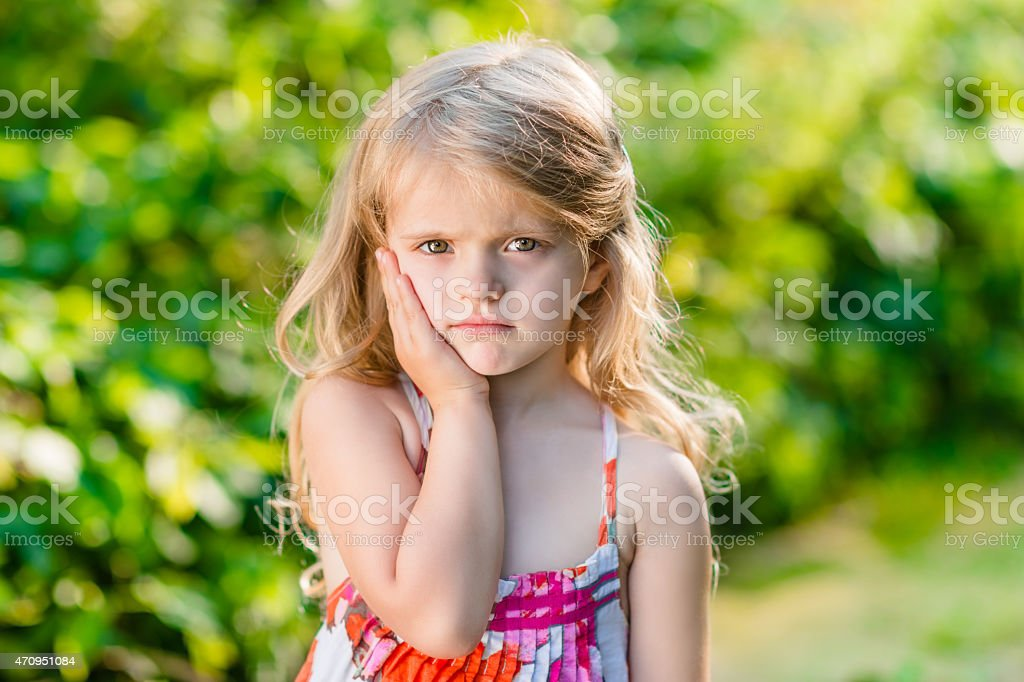 Sad little girl with long blond hair suffering from toothache stock photo