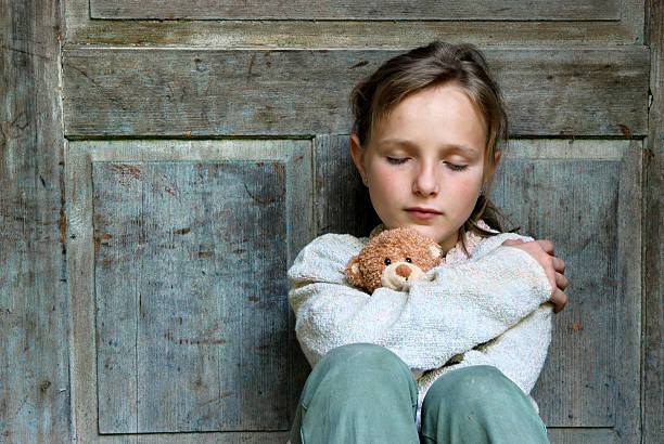 Sad little girl with teddy bear stock photo