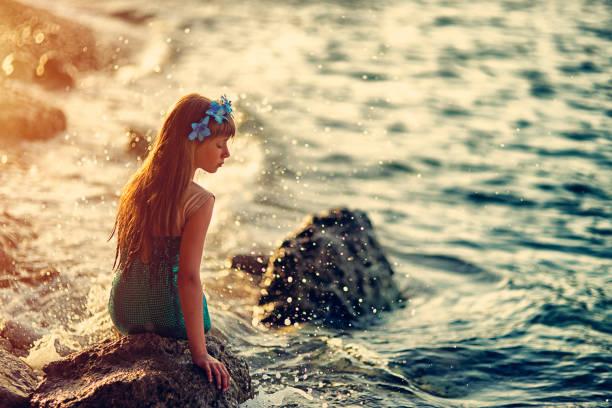 traurige kleine meerjungfrau sitzt im rock - meerjungfrau wellen stock-fotos und bilder