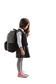 Full length profile shot of a sad little schoolgirl with a backpack isolated on white background