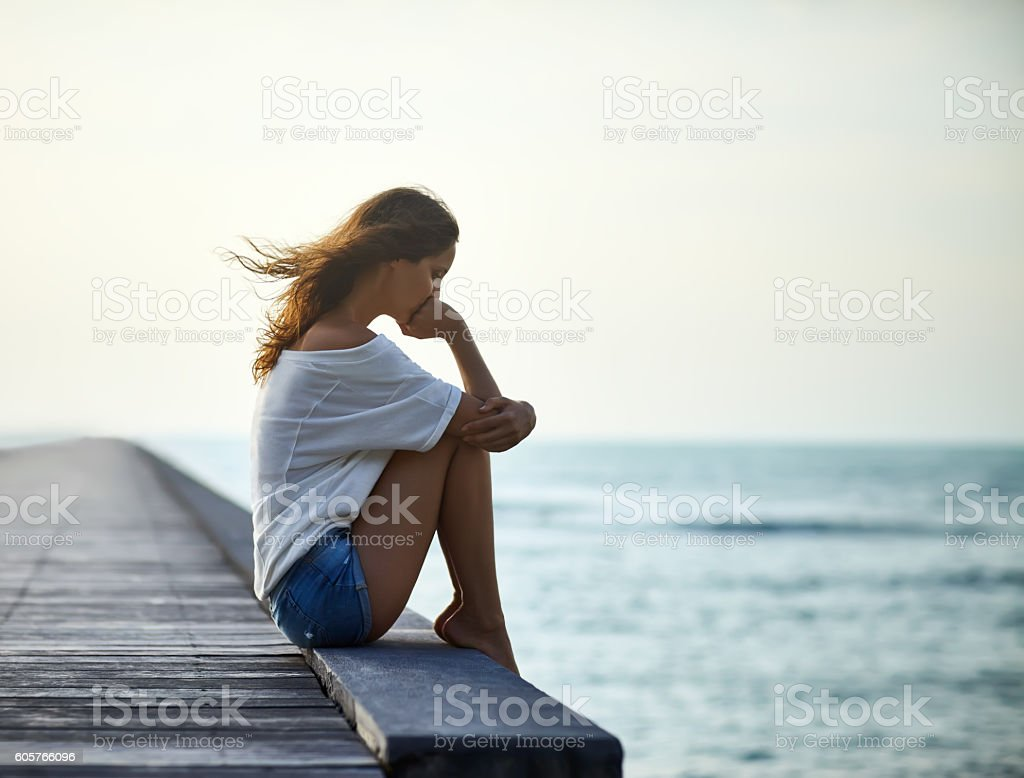 Sad lonely beautiful woman sitting on the pier stock photo