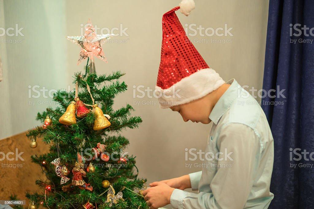 Sad lonely boy undecorating Christmas tree stock photo