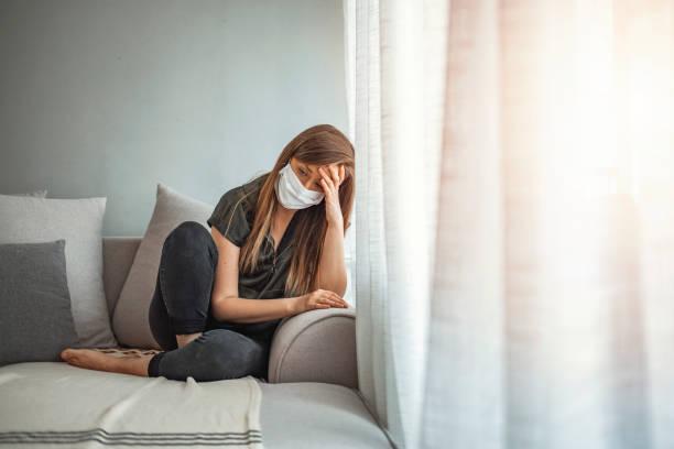 грустная одинокая девушка изолирована остаться дома в защитной стерильной медицинской маске на лице, глядя в окно - болезнь стоковые фото и изображения