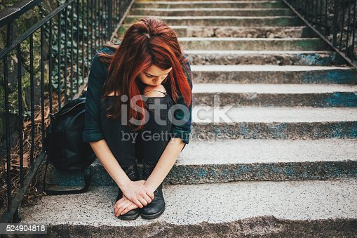 istock Sad lonely girl sitting on stairs 524904818