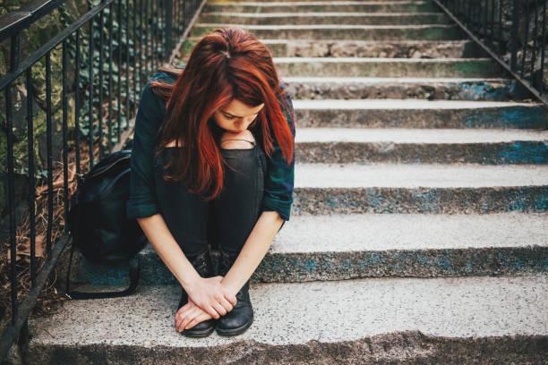 traurig einsam sitzendes mädchen auf treppe - jugendalter stock-fotos und bilder