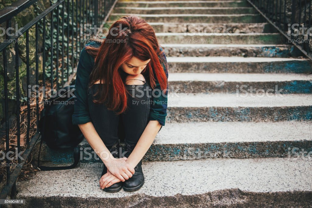 Sad lonely girl sitting on stairs stock photo