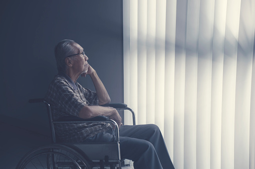 Sad lonely asian senior man sitting on wheelchair while looking at a window