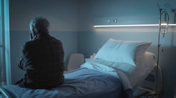 Sad lonely senior sitting in a hospital bed stock photo