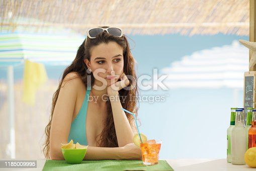 Sad young woman having a drink alone at the beach bar, she is leaning on the counter and thinking