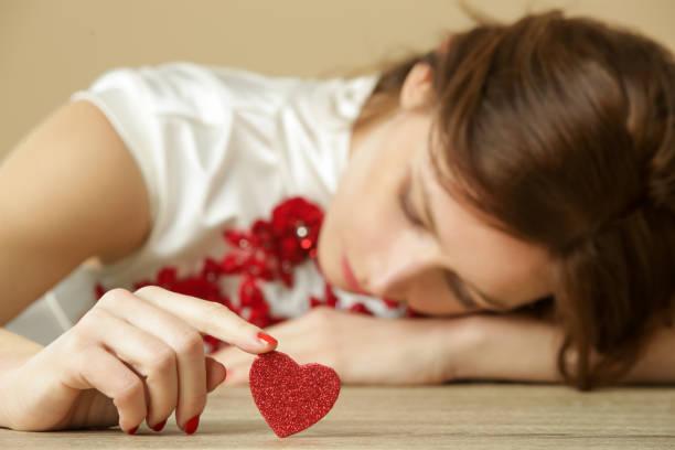 赤い心を持つ悲しい孤独な女性。 バレンタインデーに一人でいる。失恋、離婚または別れの概念。 - ロマンス ストックフォトと画像
