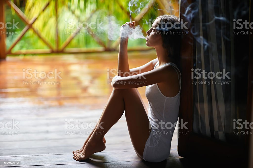 Sad lonely woman smoking cigarette and sitting on the porch stock photo