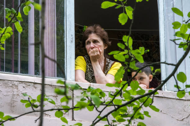 (Editorial) Sad look of a woman and her son through the window stock photo