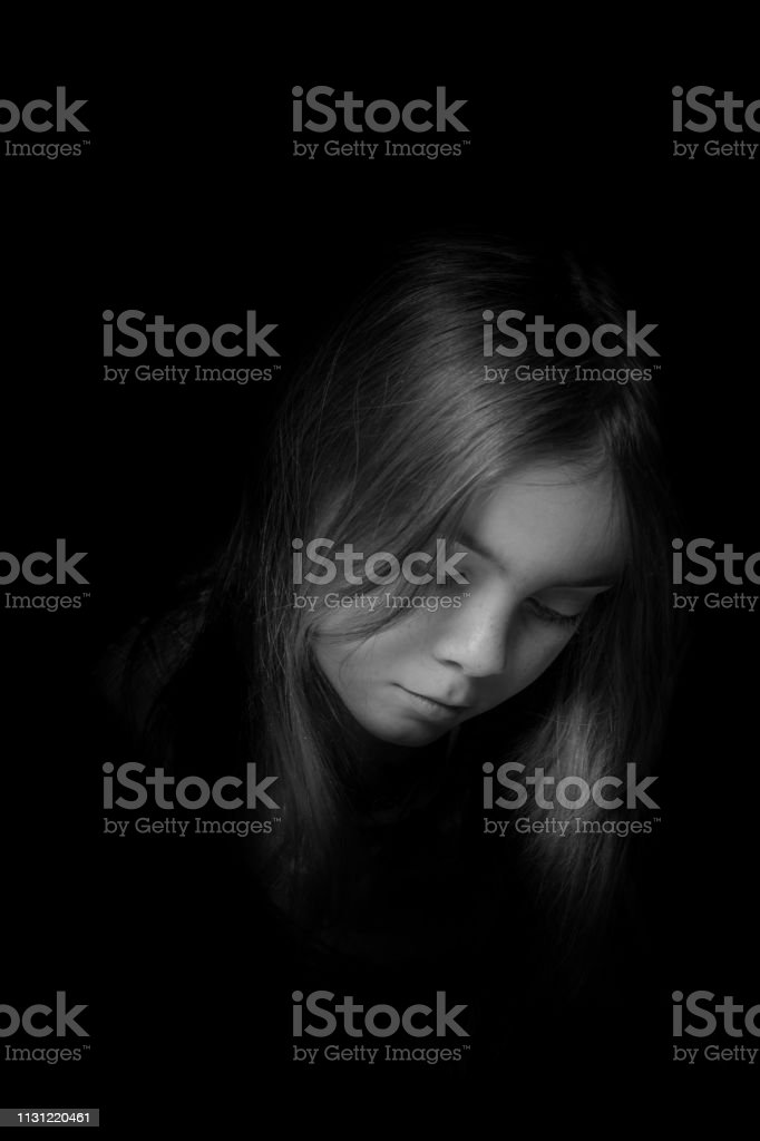Low key picrure of a girl looking sad. High contrast picture in front...