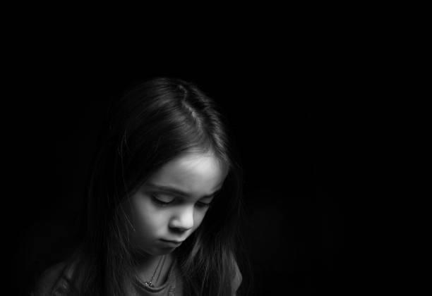 Traurig aussehende Mädchen vor schwarzem Hintergrund – Foto