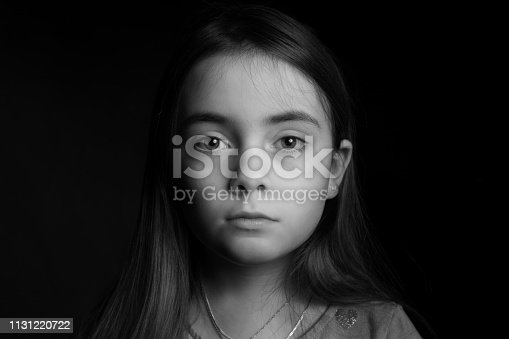 Frontal Portrait . Low key picrure of a girl looking sad straight in the camera .High contrast picture in front of a black background.