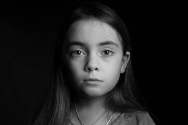 sad looking girl in front of black background - one girl only stock pictures, royalty-free photos & images
