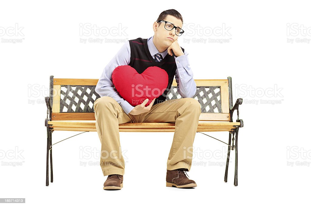 Sad male sitting on bench and holding a heart royalty-free stock photo