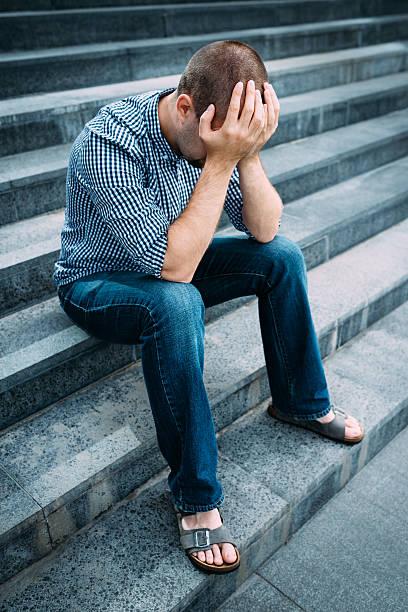 Trauriger Mann auf seinem Gesicht mit Händen sitzt auf Treppen – Foto