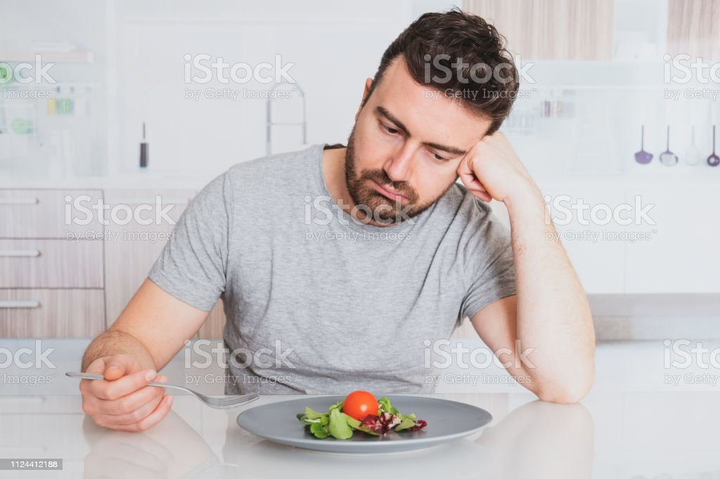 Sad man diet ready to eat salad for weight loss stock photo
