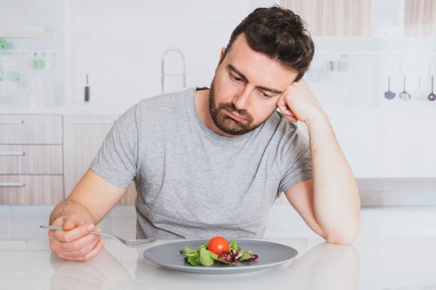 Sad man diet ready to eat salad for weight loss Worried man hungry and starved with salad hungry stock pictures, royalty-free photos & images